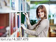 Купить «Девушка-студентка выбирает книги в библиотеке», фото № 4387479, снято 24 января 2012 г. (c) Дмитрий Калиновский / Фотобанк Лори