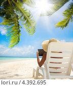 Купить «Женщина с планшетным компьютером в шезлонге под пальмами», фото № 4392695, снято 12 июля 2011 г. (c) Сергей Новиков / Фотобанк Лори