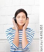 Купить «Довольная девушка в наушниках слушает музыку», фото № 4416951, снято 31 марта 2012 г. (c) Syda Productions / Фотобанк Лори