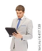 Купить «Привлекательный молодой человек в сорочке и светлом костюме с планшетным компьютером», фото № 4417139, снято 8 апреля 2012 г. (c) Syda Productions / Фотобанк Лори