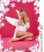 Купить «Привлекательная блондинка в образе ангела на красном фоне со снежинками», фото № 4417267, снято 23 февраля 2008 г. (c) Syda Productions / Фотобанк Лори