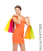 Купить «Счастливая молодая покупательница на белом фоне с пакетами», фото № 4417503, снято 31 марта 2012 г. (c) Syda Productions / Фотобанк Лори