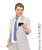 Купить «Привлекательный молодой человек в сорочке и светлом костюме с кредитной картой в руке», фото № 4417967, снято 8 апреля 2012 г. (c) Syda Productions / Фотобанк Лори