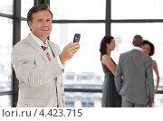 Успешный бизнесмен средних лет с сотовым телефоном в офисе. Стоковое фото, агентство Wavebreak Media / Фотобанк Лори
