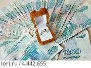 Коробочка с серебряным кольцом лежит на пачке с деньгами. Стоковое фото, фотограф Мария Деркунская / Фотобанк Лори