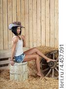 Девушка в ковбойской шляпе сидит на деревянной бочке в сарае с соломой. Стоковое фото, фотограф Игорь Долгов / Фотобанк Лори