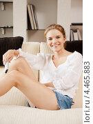 Счастливая молодая женщина смотрит в гостиной телевизор с пультом дистанционного управления в руках. Стоковое фото, фотограф Syda Productions / Фотобанк Лори
