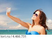 Купить «Счастливая девушка в голубом бикини фотографирует себя на телефон на пляже на фоне неба», фото № 4466731, снято 21 июля 2012 г. (c) Syda Productions / Фотобанк Лори