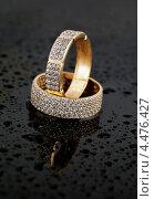 Купить «Два золотых кольца с бриллиантами на черном фоне с каплями воды», фото № 4476427, снято 11 мая 2012 г. (c) ElenArt / Фотобанк Лори