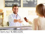 Купить «Продавец принимает к оплате кредитную карту», фото № 4483635, снято 27 января 2013 г. (c) Raev Denis / Фотобанк Лори