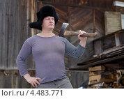 Мужчина в зимней шапке с топором у деревенского дома. Стоковое фото, фотограф Типляшина Евгения / Фотобанк Лори