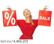 Купить «Красивая женщина в красном платье с пакетами, на которых указан процент скидки», фото № 4484259, снято 7 октября 2012 г. (c) Syda Productions / Фотобанк Лори
