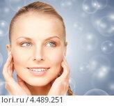 Купить «Красивая молодая женщина на сером фоне с мыльными пузырями», фото № 4489251, снято 8 мая 2010 г. (c) Syda Productions / Фотобанк Лори