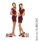 Купить «Две юные девушки в коротких темных платьях выбирают обувь в магазине», фото № 4489291, снято 28 октября 2012 г. (c) Syda Productions / Фотобанк Лори