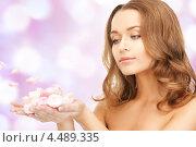Купить «Красивая девушка с распущенными волосами и цветочными лепестками в ладонях», фото № 4489335, снято 10 октября 2010 г. (c) Syda Productions / Фотобанк Лори