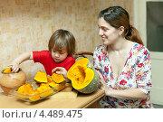 Купить «Мама с маленькой дочкой на кухне готовят тыкву», фото № 4489475, снято 26 ноября 2012 г. (c) Яков Филимонов / Фотобанк Лори