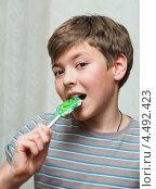Радостный мальчик-подросток ест большой леденец на палочке. Стоковое фото, фотограф Игорь Низов / Фотобанк Лори