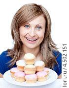 Купить «Голубоглазая блондинка с вожделением смотрит на тарелку сладких кексов», фото № 4502151, снято 23 марта 2010 г. (c) Wavebreak Media / Фотобанк Лори