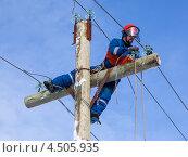 Электрик с монтажными когтями (кошками) работает на высоте без помощи подъемника. Стоковое фото, фотограф Александр Новиков / Фотобанк Лори