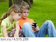 Купить «Брат и сестра сидят в парке на траве и смотрят на экран смартфона», фото № 4515299, снято 18 июля 2011 г. (c) Losevsky Pavel / Фотобанк Лори