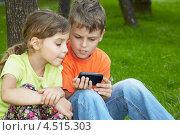 Купить «Мальчик и девочка сидят в парке на траве и смотрят на экран смартфона», фото № 4515303, снято 18 июля 2011 г. (c) Losevsky Pavel / Фотобанк Лори