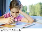 Купить «Недовольная девочка сидит у окна в скоростном поезде и рисует ручкой в цветном журнале», фото № 4515347, снято 19 июля 2011 г. (c) Losevsky Pavel / Фотобанк Лори