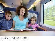 Купить «Мама читает детям книгу в поезде», фото № 4515391, снято 19 июля 2011 г. (c) Losevsky Pavel / Фотобанк Лори