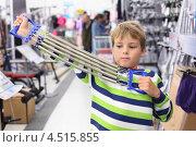 Купить «Мальчик в полосатом свитере растягивает руками эспандер в спортивном магазине», фото № 4515855, снято 10 сентября 2011 г. (c) Losevsky Pavel / Фотобанк Лори