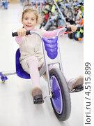 Купить «Счастливая девочка едет на трехколесном велосипеде в спортивном магазине», фото № 4515899, снято 10 сентября 2011 г. (c) Losevsky Pavel / Фотобанк Лори