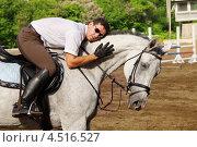 Купить «Жокей в очках обнимает свою лошадь на ипподроме», фото № 4516527, снято 10 июня 2011 г. (c) Losevsky Pavel / Фотобанк Лори