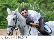 Купить «Жокей в очках с хлыстом на лошади на ипподроме», фото № 4516547, снято 10 июня 2011 г. (c) Losevsky Pavel / Фотобанк Лори