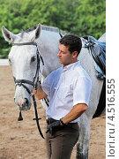 Купить «Мужчина жокей в перчатках обнимает лошадь на ипподроме», фото № 4516555, снято 10 июня 2011 г. (c) Losevsky Pavel / Фотобанк Лори