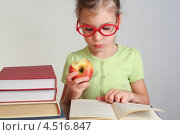 Купить «Серьезная девочка читает книгу и ест яблоко», фото № 4516847, снято 7 ноября 2011 г. (c) Losevsky Pavel / Фотобанк Лори