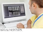 Купить «Стоматолог в жёлтом халате перед компьютером с рентгеновским снимком зубов», фото № 4517675, снято 25 июня 2011 г. (c) Losevsky Pavel / Фотобанк Лори