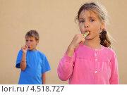 Купить «Мальчик и девочка с разноцветными конфетами на бежевом фоне», фото № 4518727, снято 22 августа 2011 г. (c) Losevsky Pavel / Фотобанк Лори