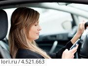 Купить «Девушка набирает смс за рулем», фото № 4521663, снято 17 мая 2010 г. (c) Wavebreak Media / Фотобанк Лори