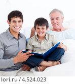 Купить «Дед, отец и сын с книгой на постели», фото № 4524023, снято 2 октября 2009 г. (c) Wavebreak Media / Фотобанк Лори