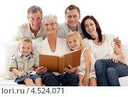 Купить «Пожилая женщина с книгой в окружении родственников», фото № 4524071, снято 26 марта 2019 г. (c) Wavebreak Media / Фотобанк Лори