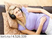 Купить «Девушка слушает в наушниках музыку на диване, улыбаясь», фото № 4526339, снято 15 марта 2010 г. (c) Wavebreak Media / Фотобанк Лори