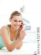 Девушка говорит по мобильному телефону и держит в руке кредитную карту. Стоковое фото, агентство Wavebreak Media / Фотобанк Лори