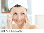 Купить «Девушка мажет кремом возле глаз», фото № 4530707, снято 7 июня 2010 г. (c) Wavebreak Media / Фотобанк Лори