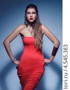 Купить «Стройная блондинка в красном платье стоит на синем фоне», фото № 4545383, снято 2 марта 2013 г. (c) Михайлов Виталий / Фотобанк Лори