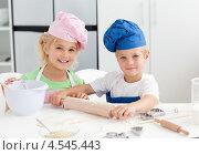 Купить «Радостные брат и сестра в поварских колпаках раскатывают тесто на кухне», фото № 4545443, снято 27 октября 2010 г. (c) Wavebreak Media / Фотобанк Лори