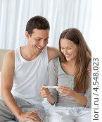 Купить «Счастливая пара смотрит на результаты теста на беременность сидя на кровати», фото № 4548023, снято 23 октября 2010 г. (c) Wavebreak Media / Фотобанк Лори