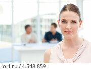 Купить «Серьезная деловая женщина в офисе. На заднем плане сотрудники за столом», фото № 4548859, снято 28 октября 2010 г. (c) Wavebreak Media / Фотобанк Лори