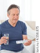 Купить «Пожилой мужчина со стаканом воды и таблетками», фото № 4558875, снято 30 октября 2010 г. (c) Wavebreak Media / Фотобанк Лори
