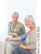 Купить «Молодая медсестра измеряет кровяное давление у пожилой женщины», фото № 4560663, снято 1 ноября 2010 г. (c) Wavebreak Media / Фотобанк Лори