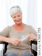 Купить «Пожилая женщина в инвалидной коляске держит в руках упаковку таблеток», фото № 4560755, снято 1 ноября 2010 г. (c) Wavebreak Media / Фотобанк Лори