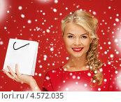 Купить «Красивая блондинка в красном платье с покупкой в белом пакете», фото № 4572035, снято 7 октября 2012 г. (c) Syda Productions / Фотобанк Лори