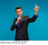 Купить «Привлекательный молодой человек в темном костюме руками работает с виртуальным цифровым экраном», фото № 4572527, снято 17 ноября 2012 г. (c) Syda Productions / Фотобанк Лори